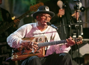 an older african american man sitting down playing a guitar