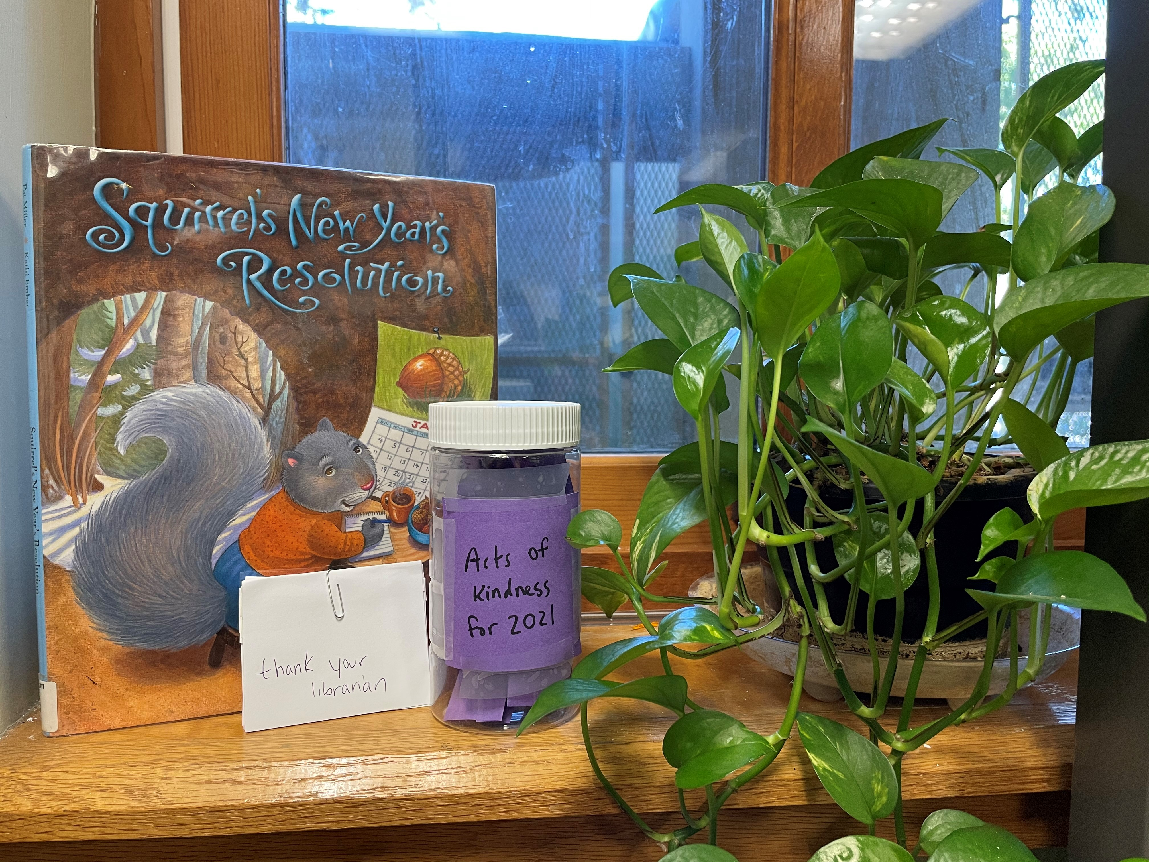 """Picture of book """"Squirrel's New Year's Resolutions"""" with jar labeled """"Acts of Kindness for 2021"""" and a plant"""