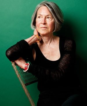 A picture of poet, Louise Gluck, wearing a black dress with a green background.